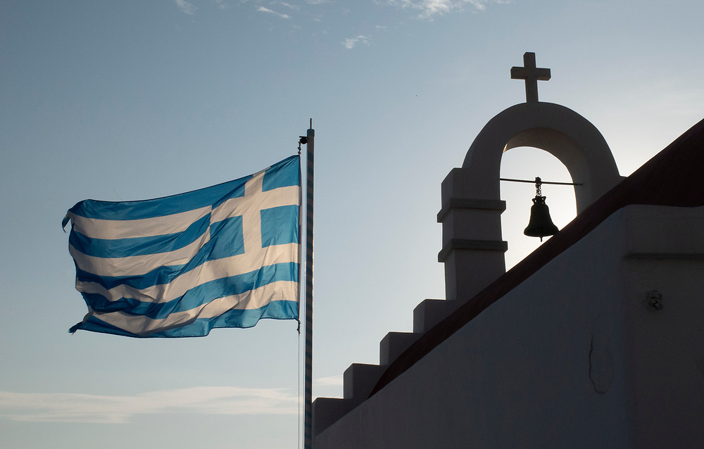 Backlit Greek flag blowing in the wind over one of the many churches in Mykonos Town, Greece