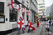Medieval knights on an afternoon pub crawl on St Georges Day on 23rd April 2018 in London, England, United Kingdom. Wearing chainmail, St Georges Cross shields and flags, this type of dressing up has become popular as a sign of patriotism and fun as groups go out drinking on Englands national day.