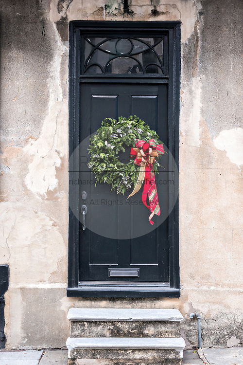 An evergreen Christmas wreath decorates a wooden door on a historic home at Tradd Street in Charleston, SC.