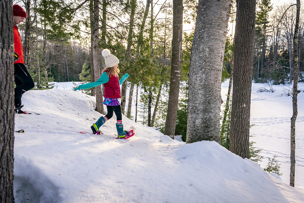 A young family snowshoes in the woods near Marquette, Michigan.