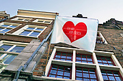 Nederland, Nijmegen, 30-4-2020 Aan de gevel van een huis in de oude binnenstad is een vlag met  een rood hart opgehangen als dank en respectbetuiging aan het personeel in de zorg en op de ic die met het coronavirus te maken hebben . Foto: Flip Franssen