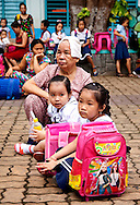 Two sisters look unhappy as they wait with their grandmother to be called to classes. Backpacks with western cartoon and action figures are very popular with students. Robert Dodge, a Washington DC photographer and writer, has been working on his Vietnam 40 Years Later project since 2005. The project has taken him throughout Vietnam, including Hanoi, Ho Chi Minh City (Saigon), Nha Trang, Mue Nie, Phan Thiet, the Mekong, Sapa, Ninh Binh and the Perfume Pagoda. His images capture scenes and people from women in conical hats planting rice along the Red River in the north to men and women working in the floating markets on the Mekong River and its tributaries. Robert's project also captures the traditions of ancient Asia in the rural markets, Buddhist Monasteries and the celebrations around Tet, the Lunar New Year. Also to be found are images of the emerging modern Vietnam, such as young people eating and drinking and embracing the fashions and music of the West. His book. Vietnam 40 Years Later, was published March 2014 by Damiani Editore of Italy.