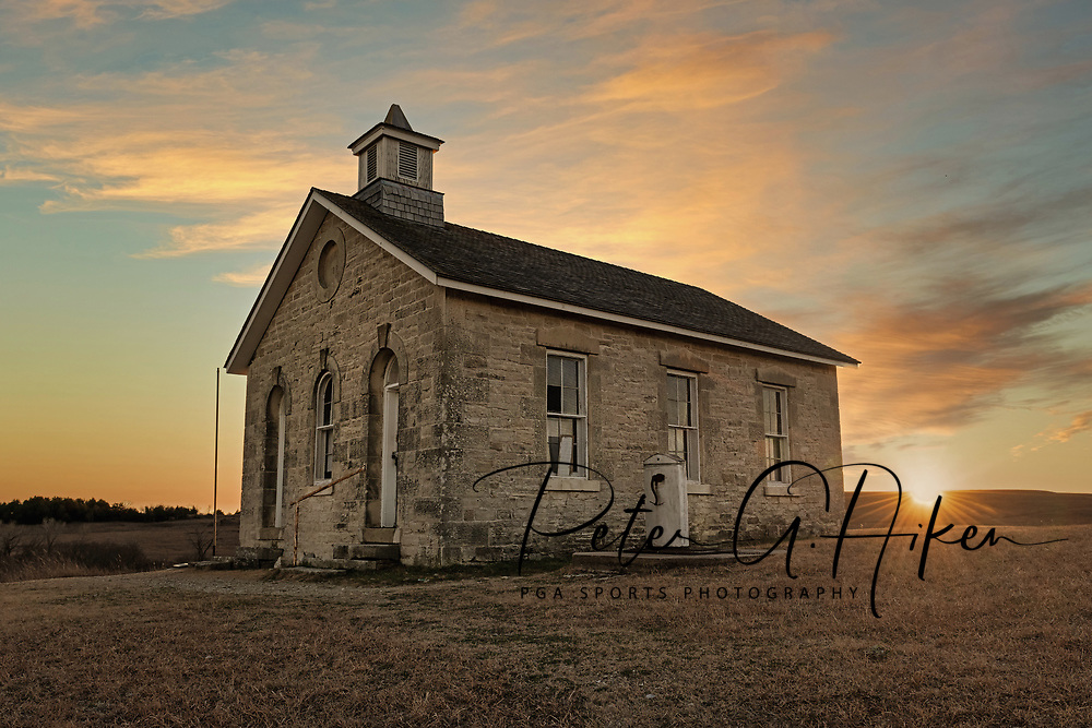 An autumn sunset at the Lower Fox Creek School in the Tallgrass Prairie of the Flint Hills.  The school was built in 1884 of natural limestone and was an example of the common school. The model of the common school proposed by Horace Mann was embraced by Kansans when it was time to organize schools in the new territory (and later the state) of Kansas.