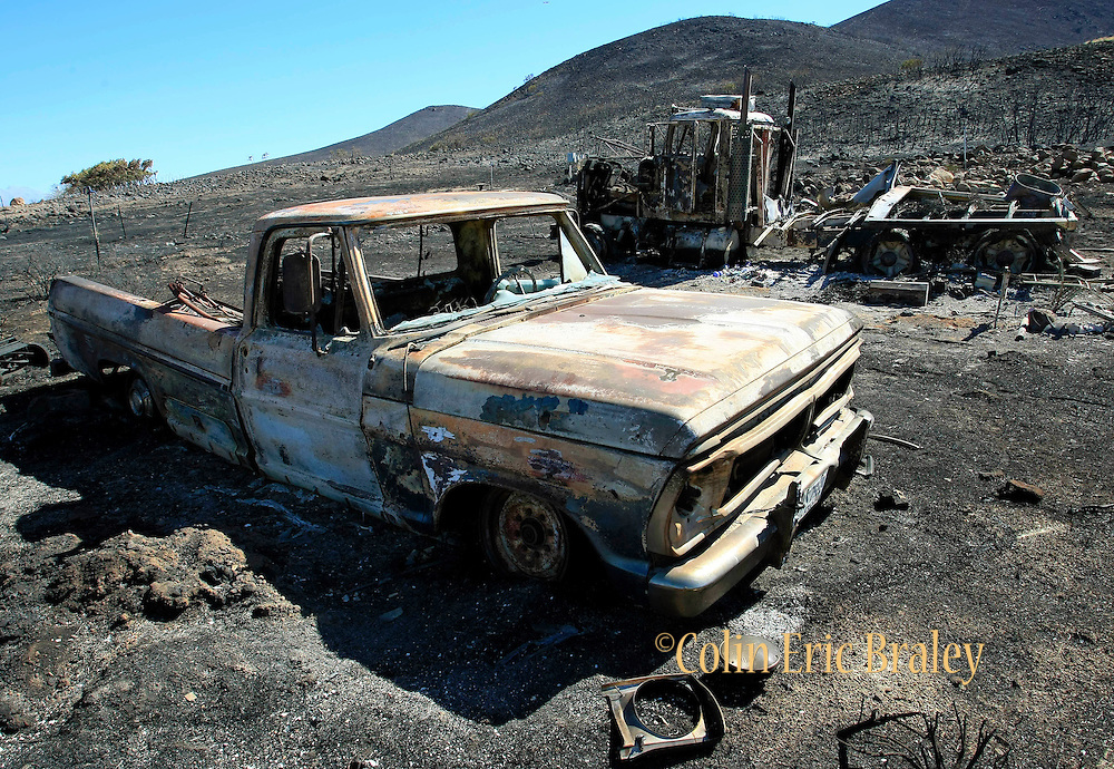 Burned out trucks and thousands of acres of charred brush are all that remains after a wildfire destroyed three homes and forced the evacuation of over 1,600 homes Monday, Sept. 20, 2010, in Herriman, Utah. The blaze was started by live-fire exercises at Camp Williams, a Army National Guard base southwest of Salt Lake City.. (AP Photo/Colin E. Braley)