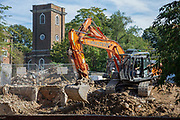A church steeple can be seen behind men using a digging machine on a demolition site in London, United Kingdom on 13th September 2019.