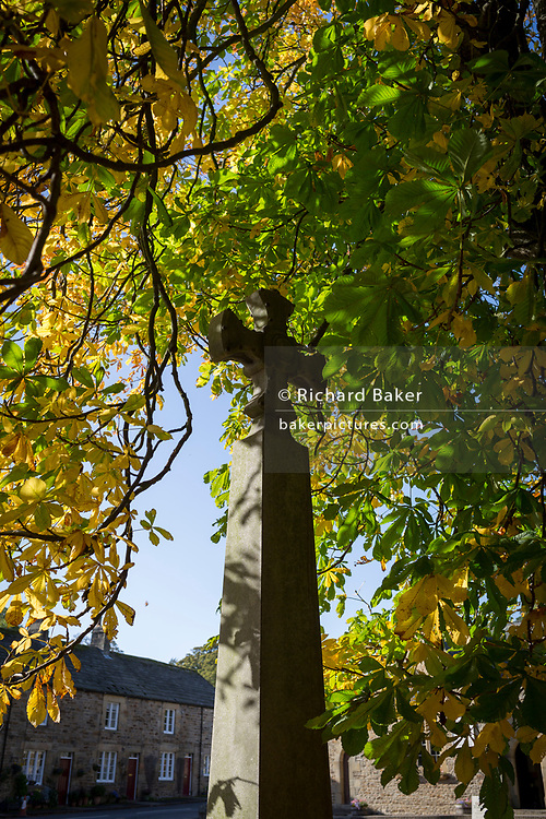 The war memorial in the churchyard of St Mary's in the Northumbrian village of Blanchland, on 29th September 2017, in Blanchland, Northumberland, England. St. Marys is on the site of the former Abbey and the village got its name from the white habits worn by monks of the Premonstratensian order who founded Blanchland Abbey. Built in the 13th century, the abbey survived until the 16th century when it fell into ruin. Parts of the Abbey survive including St. Mary's Church, which was rebuilt in 1751-52. Blanchland is a village in Northumberland, England, on the County Durham boundary. It is a conservation village, largely built of stone from the remains of the 12th-century Abbey. It features picturesque houses, set against a backdrop of deep woods and open moors. Set beside the river in a wooded section of the Derwent valley, Blanchland is an attractive small village in the North Pennines Area of Outstanding Natural Beauty.