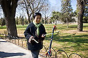 Woman practises tai chi with sticks in park of the Temple of Heaven, Beijing, China