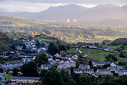 With the nuclear power station of Trawsfynydd seen in the distance, houses in the southern part of Blaenau Ffestiniog, on 3rd October 2021, in Blaenau Ffestiniog, Gwynedd, Wales. The derelict slate mines around Blaenau Ffestiniog in north Wales were awarded UNESCO World Heritage status in 2021. The industry's heyday was the 1890s when the Welsh slate industry employed approximately 17,000 workers, producing almost 500,000 tonnes of slate a year, around a third of all roofing slate used in the world in the late 19th century. Only 10% of slate was ever of good enough quality and the surrounding mountains now have slate waste and the ruined remains of machinery, workshops and shelters have changed the landscape for square miles.