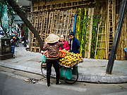 "24 DECEMBER 2017 - HANOI, VIETNAM: A produce vender sells her products in front of a bamboo shop in the old quarter of Hanoi. The old quarter is the heart of Hanoi, with narrow streets and lots of small shops but it's being ""gentrified"" because of tourism and some of the shops are being turned into hotels and cafes for tourists and wealthy Vietnamese.           PHOTO BY JACK KURTZ"