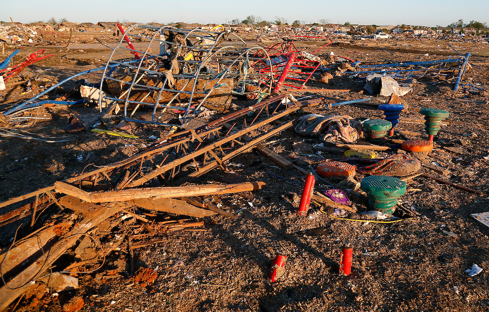 The playground equipment outside the Plaza Towers elementary school where seven children died in a tornado is covered in debris in Moore, Oklahoma May 22, 2013.  Rescue workers with sniffer dogs picked through the ruins on Wednesday to ensure no survivors remained buried after a deadly tornado left thousands homeless and trying to salvage what was left of their belongings.  REUTERS/Rick Wilking (UNITED STATES)