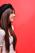 Portrait of a Young stylish 18 year old female teen happy and cheeky on red background