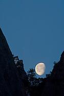 Waning gibbous moon setting behind mountain cliff, Yosemite National Park, California