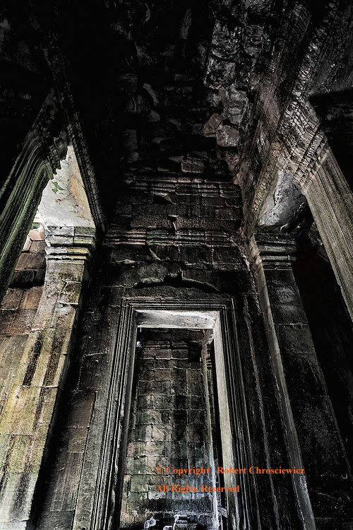 Ruins at Angkor Wat, Cambodia: Dark and moody view of high vaulted ceilings of an entrance in the ancient ruins at Angkor Wat, Cambodia.