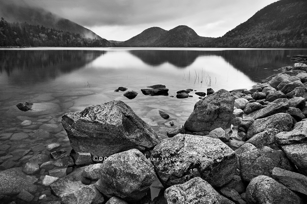 Jordan Pond on a cool autumn evening at Acadia National Park with two mountains called The Bubbles in the background and boulders in the foreground,, Maine, USA