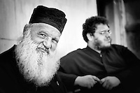 Black and white photo of two priests in Mykonos, Greece.
