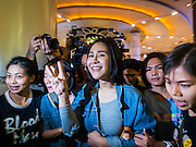 20 NOVEMBER 2014 - BANGKOK, THAILAND: Plainclothes female Thai police officers lead NATCHACAH KONG-UDOM (center) away while arresting her for speaking out against the coup and displaying the three fingered salute from the Hunger Games movies. Kong-Udom was one of at least three people arrested by Thai police during the opening the Hunger Games: Mockingjay - Part 1 in Bangkok Thursday. Opponents of the Thai military coup have adapted the three fingered salute used in the Hunger Games series as a sign of their opposition to the coup. In the weeks before the movie opening Thai police arrested several people for using the Hunger Games salute and Thai media reported that one Thai movie theater chain cancelled plans to show the movie at the request of the military government. There were several small protests at theaters showing the movie Thursday.     PHOTO BY JACK KURTZ