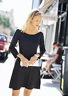 This image was shot on loacation in Charleston: a young lady is window shoing at a local store front, wearing a classic little black dress.