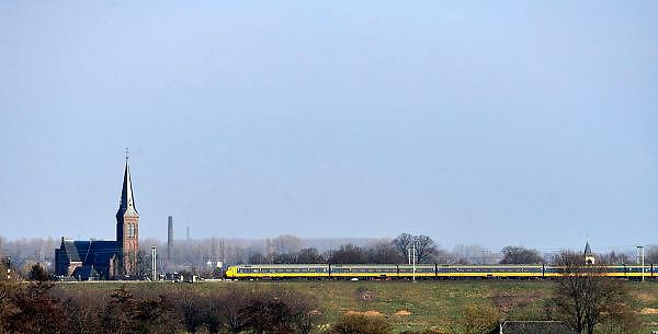 Nederland, Nijmegen, 6-3-2014Een lange trein rijdt tijdens de spits, avondspits, door het landschap en langs een kerk op het traject naar Arnhem.Foto: Flip Franssen/Hollandse Hoogte