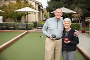 Senior couple looking at camera playing bocce ball
