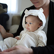 A two month old baby girl watches an interactive app for babies on an iPad while held by her mother. Photo Tim Clayton