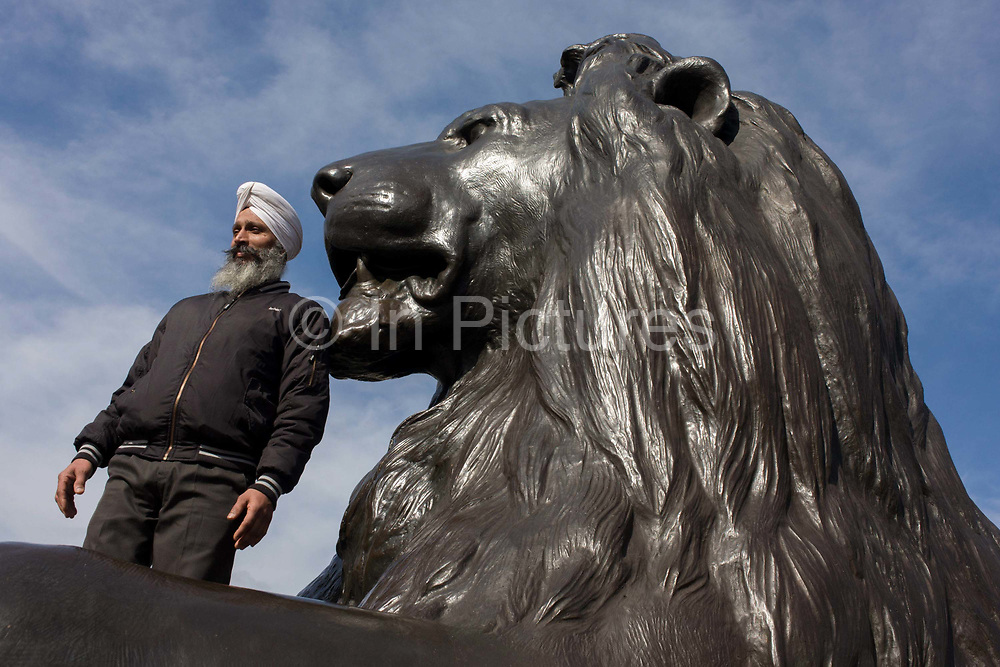 A Sikh man stands under one of the four lions at the base of Nelson's Column in London's Trafalgar Square. As a symbol of a multi-racial, multi-ethnic Britain, we see the man from Indian descent, beneath another symbol - that of a bygone British Empire, from an era of expansion, trade and rule over the British Raj. The lion is below the memorial to Lord Haratio Nelson, Britain's navel hero who died in the Battle of Trafalgar during the Napoleonic wars, in 1805.
