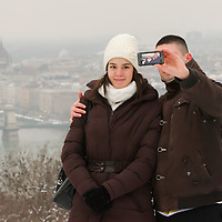 Tourist couple takes self photo with the view of the city center in the background in Budapest, Hungary on January 19, 2013. ATTILA VOLGYI