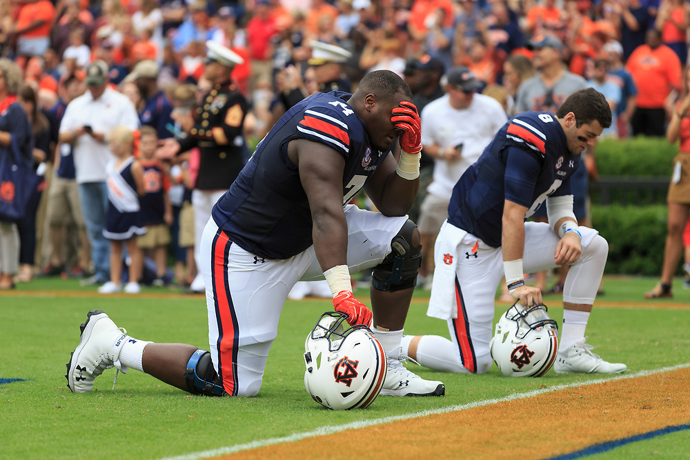 Auburn Tigers offensive lineman Wilson Bell (74) and quarterback Jarrett Stidham (8) kneel and pray prior to an NCAA football game against the Mississippi Rebels, Saturday, October 7, 2017, in Auburn, AL. Auburn won 44-23. (Paul Abell via Abell Images for Chick-fil-A Peach Bowl)
