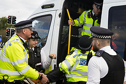 Colnbrook, UK. 27th September, 2021. Metropolitan Police officers arrest an Insulate Britain climate activist who had previously blocked a M25 slip road at Junction 14 close to Heathrow airport as part of a campaign intended to push the UK government to make significant legislative change to start lowering emissions. The activists are demanding that the government immediately promises both to fully fund and ensure the insulation of all social housing in Britain by 2025 and to produce within four months a legally binding national plan to fully fund and ensure the full low-energy and low-carbon whole-house retrofit, with no externalised costs, of all homes in Britain by 2030.
