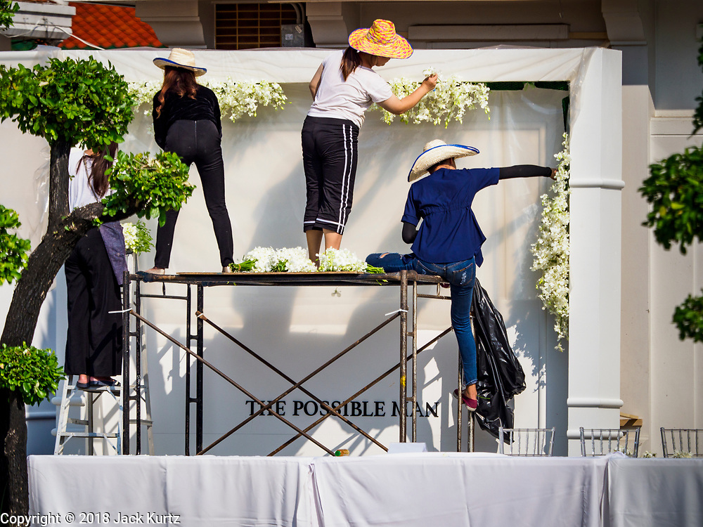 """04 NOVEMBER 2018 - BANGKOK, THAILAND: Workers put the decorations for the funeral of Vichai Srivaddhanaprabha at Wat Debsirin on the second day of funeral rites for Vichai. The """"Possible Man"""" reflects Vichai's legacy in Leicester because he was viewed as the man who made everything possible after Leicester won the 2015-16 Premier League Championship. Vichai was the owner of King Power, a Thai duty free conglomerate, and the Leicester City Club, a British Premier League football (soccer) team. He died in a helicopter crash at the King Power stadium in Leicester after a match on October 27. Vichai was Thailand's 5th richest man. The funeral is expected to last one week.  PHOTO BY JACK KURTZ"""
