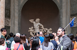 Tourist tour group looking at The Laocoön group sculpture at the Vatican Museum in Rome, Italy