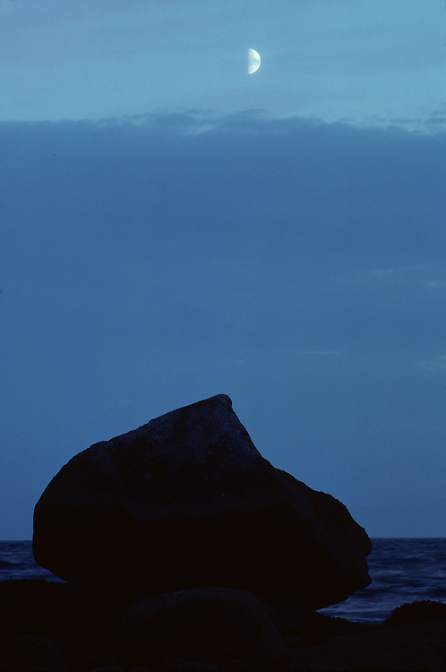 Ireland, Gibbous moon rises above rocky shoreline in County Galway on autumn evening