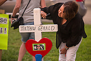Woman writes a message on a cross at a makeshift memorial where six oifficers were shot on Airline Highway in Baton Rouge. Three of the officers were killed and another one remains in criticial condition. The memorial in from of the  B-Quik gas station  continues to grow.