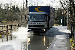 """© Licensed to London News Pictures. 07/02/2014; Stanley Downton, near Stonehouse, Gloucestershire, UK.  River flooding makes for slow driving for lorry with """"rainbows"""" on it at the village of Stanley Downton.<br /> 07 February 2014.<br /> Photo credit: Simon Chapman/LNP"""