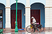 A man rides a bicycle past the colorful city hall in Tlacotalpan, Veracruz, Mexico. The tiny town is painted a riot of colors and features well preserved colonial Caribbean architectural style dating from the mid-16th-century.