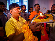 "23 SEPTEMBER 2018 - BANGKOK, THAILAND: A man makes an offering at the Ganesha Festival at Wat Dan in Bangkok. Ganesha Chaturthi also known as Vinayaka Chaturthi, is the Hindu festival celebrated on the day of the re-birth of Lord Ganesha, the son of Shiva and Parvati. The festival, also known as Ganeshotsav (""festival of Ganesha"") is observed in the Hindu calendar month of Bhaadrapada, starting on the the fourth day of the waxing moon. The festival lasts for 10 days, ending on the fourteenth day of the waxing moon. Outside India, it is celebrated widely in Nepal and by Hindus in the United States, Canada, Mauritius, Singapore, Thailand, Cambodia, and Burma.    PHOTO BY JACK KURTZ"