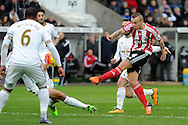 Southampton's Jordy Clasie (4) has his shot at goal blocked by Swansea's Jack Cork (green boots). Barclays Premier league match, Swansea city v Southampton at the Liberty Stadium in Swansea, South Wales on Saturday 13th February 2016.<br /> pic by  Carl Robertson, Andrew Orchard sports photography.
