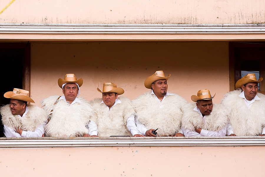Men dressed in the traditional homespun white wool tunics stand on a balcony overlooking the plaza during the festival for San Juan Bautista in the Tzotzil Mayan village of San Juan Chamula, outside of San Cristobal de las Casas, Chiapas state, Mexico on June 24, 2008.