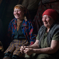 """During a rare time to relax, north of the Arctic Circle in Russia,  women of the last nomadic Komi reindeer herding clan gather for tea and biscuits in Marie Terentéva's chum.  Left to Right:  Katerina (""""Katya"""") Vaucheskaya,  Rema Chuprova  & Marie Terentéva."""