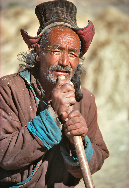 A weather-wizened farmer leans on his pitchfork during a pause from winnowing grain near Leh, Ladakh, India.
