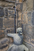 With contemporary electrical cables emerging from a wall above, a stone figure is propped up in the corner of historical walls, on 26th September 2017, in Alnwick, Northumberland, England.