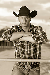 portrait of a young good looking green eyed cowboy outdoors on a ranch