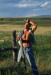 Sexy muscular ranch hand wiping sweat from his forehead after repairing a barbed wired fence in New Mexico