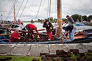 "Ciara Malone amoung the crewmembers unloading the turf from ""Capall"" ,the oldest boat taking part in the Crinniú na mBad,Kinvara,Co Galway at the weekend. Photograph by Eamon Ward"
