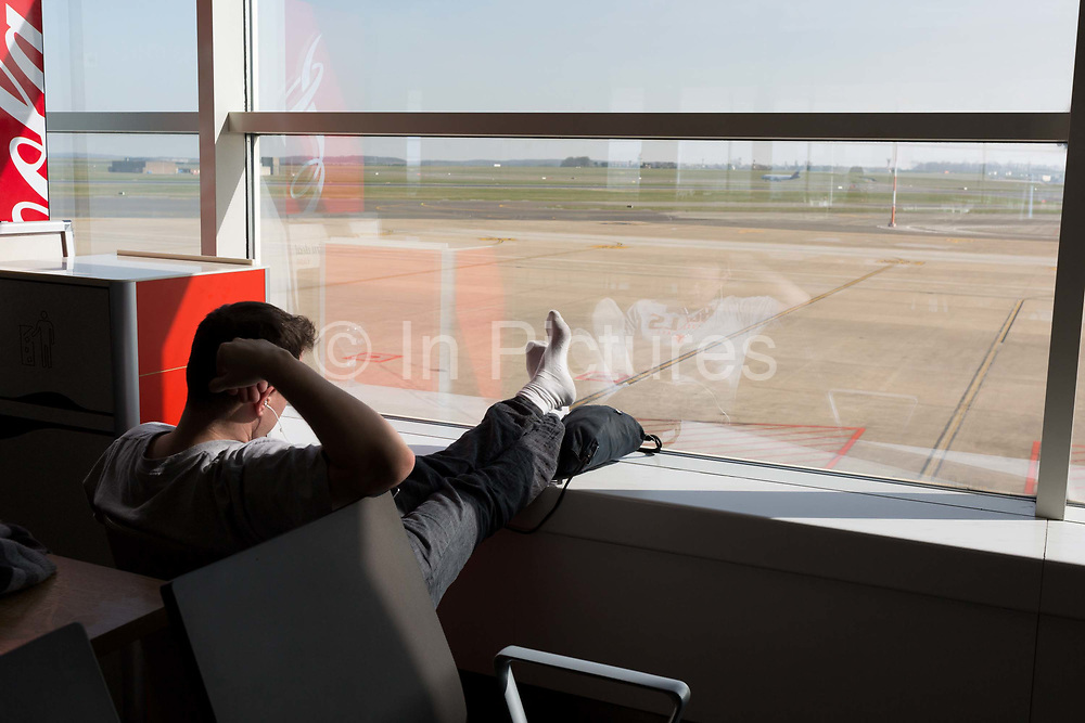 An airline passenger awaits his flight, on 26th March 2017, at Brussels Airport, Zaventem, Belgium.