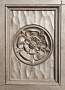 Historic carved Tudor rose on wooden panel on door of house in Marlborough, Wiltshire, England, UK