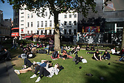 Tourists lazing around on the grass in Leicester Square in the West End of London, England, United Kingdom.