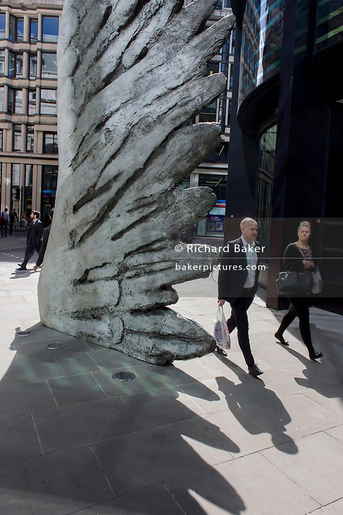 City workers pass-by the giant artwork of a bronze wing<br /> during a spring lunchtime in London's financial district. As light reflects off nearby office buildings, the lunchtime crowd walk past this giant artwork on their way to meetings and sandwich bars. The ten-metre-tall bronze sculpture is by President of the Royal Academy of Arts, Christopher Le Brun, commissioned by Hammerson in 2009. It is called 'The City Wing' and has been cast by Morris Singer Art Founders, reputedly the oldest fine art foundry in the world.