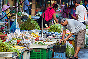 """26 SEPTEMBER 2012 - BANGKOK, THAILAND:  A man shops for produce in Klong Toey Market in Bangkok. Klong Toey (also called Khlong Toei) Market is one of the largest """"wet markets"""" in Thailand. The market is located in the midst of one of Bangkok's largest slum areas and close to the city's original deep water port. Thousands of people live in the neighboring slum area. Thousands more shop in the sprawling market for fresh fruits and vegetables as well meat, fish and poultry.    PHOTO BY JACK KURTZ"""