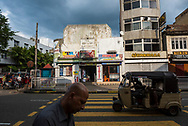A pedestrian and auto-rickshaw move through the city center of Kandy, Sri Lanka. A pharmacy and store is across the street. (April 1, 2017)