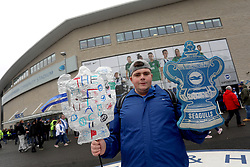 A Brighton and Hove Albion fan holds a tin foil trophy outside the ground before the FA Cup fourth round match at the AMEX Stadium, Brighton.